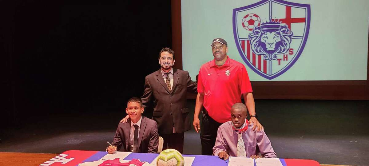 Alief Taylor soccer coach Jose Leal (back left), campus athletic coordinator Shawn Gray (back right), senior Chris Orellana (front left) and senior Malachi Redhead (front right) celebrated signing day June 1 in the Taylor High School auditorium.