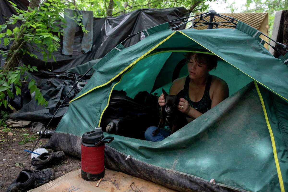 A reader supports an increased police presence downtown to address homelessness, and cautions against policies seen in some other cities. Here, a woman rests in her tent in a homeless encampment in June.