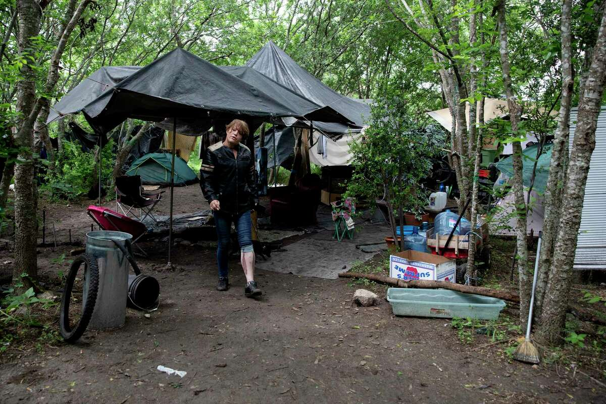 """Samantha Ade, who goes by """"Sunshine,"""" walks from an encampment she has been living in to get food from a city outreach worker."""