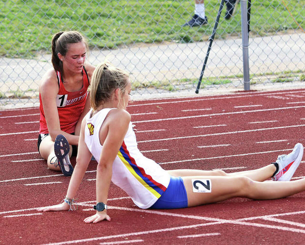 Roxana's Janelynn Wirth and Staunton's Lydia Roller (left) talk while sitting on the track just beyond the finish line after they ran 1-2 in the 3,200 meters at the EA-WR Sectional on Friday. Both will run in the event at the Class 2A state meet.
