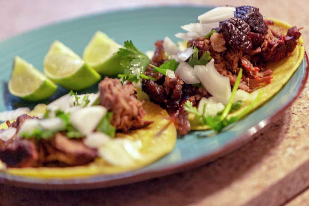 A finished plate of smoked beef cheeks with slices of lime, onions, cilantro and corn tortillas.