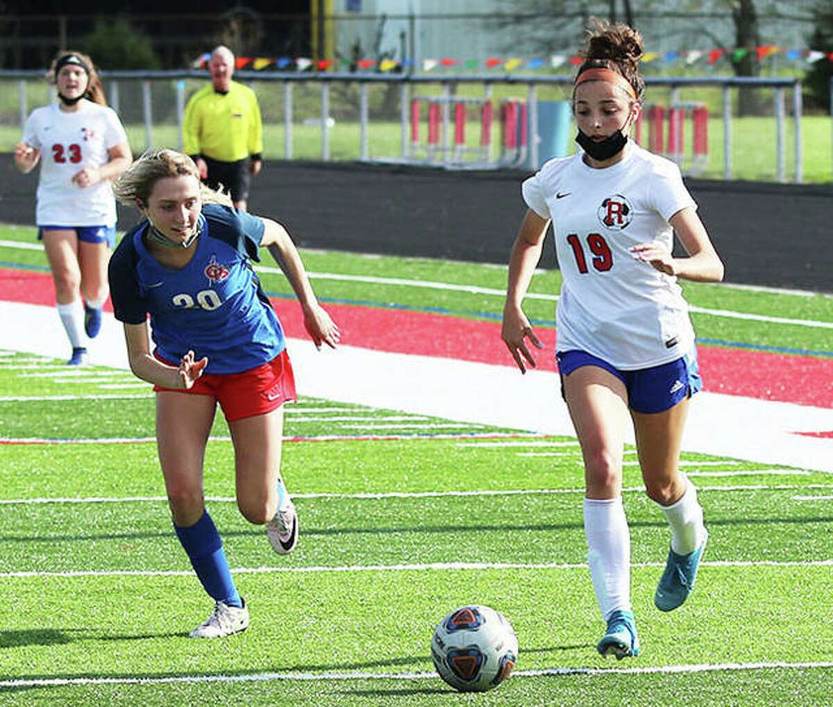 Jillian Slayton of Carlinville, left, eyes the ball as Roxana's Kendall Kamp dribbles in South Central Conference action earlier this season at Carlinville.