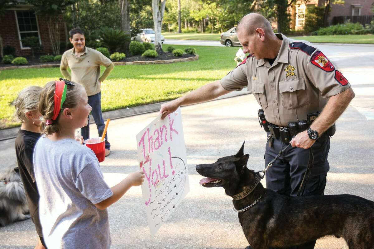 Sgt. David Birch, Montgomery County Sheriff's Office, holds K-9 police dog, Hummer, as two young residents present him with a thank you poster during a National Night Out event. Birch and Hummer will be honored by SPCA PETS SNAP MC on June 21.