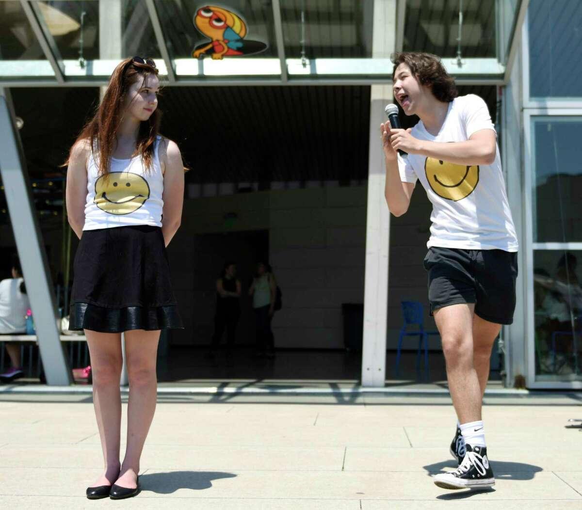 Stamford High School junior Alex Rubin, right, sings