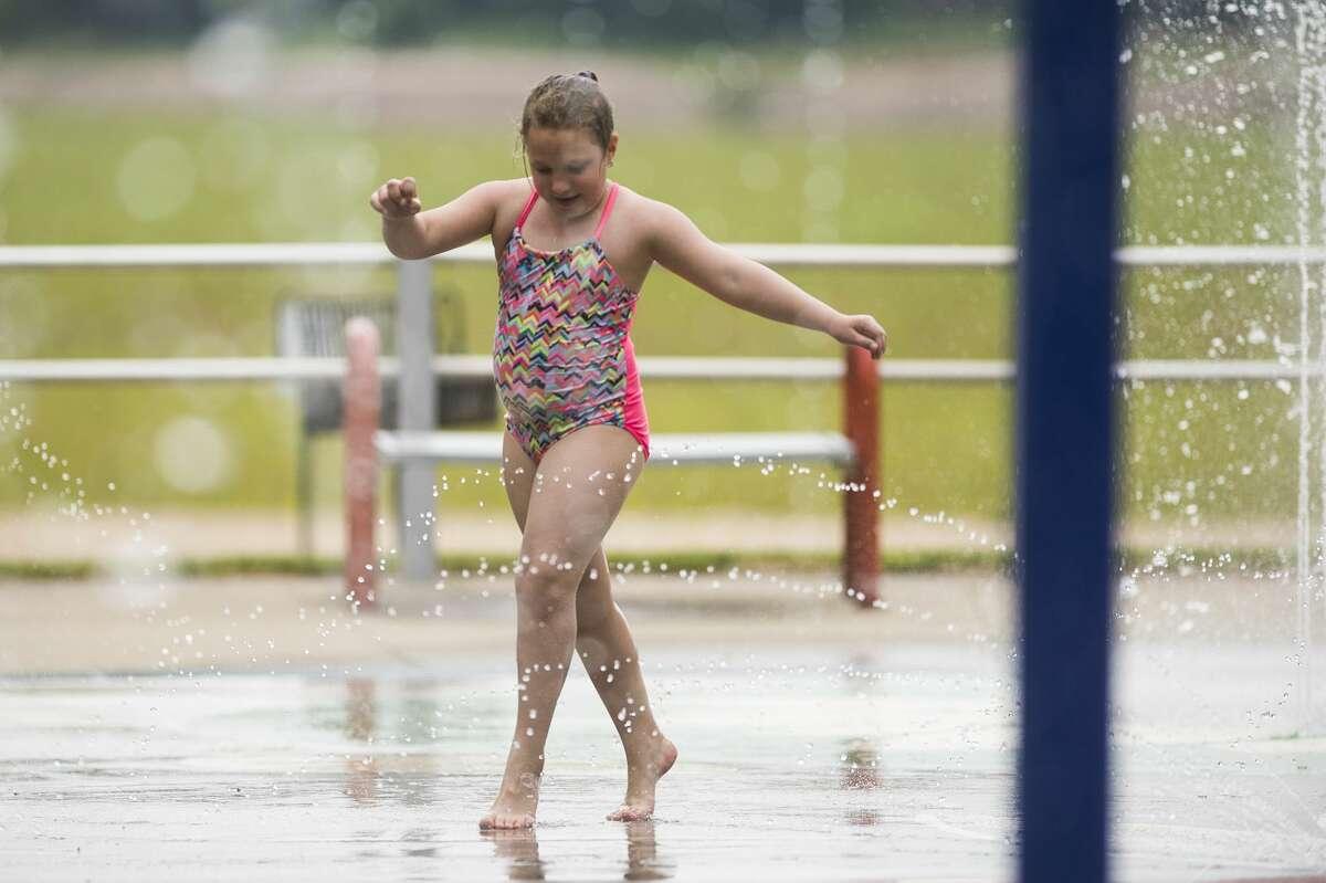 Gracelyn Bergman, 8, plays in the spray park at Sanford Lake Park Monday, June 7, 2021 in Sanford. (Katy Kildee/kkildee@mdn.net)
