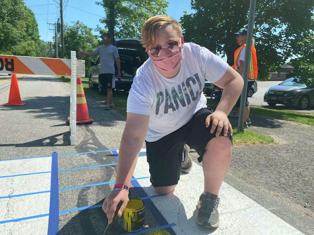 Luke Lombardi, 15, helping to repaint a crosswalk in Pride colors.