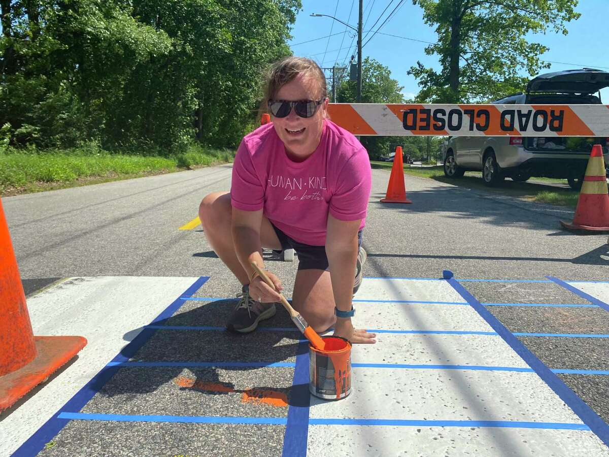 Julie Lombardi repaints Litchfield's rainbow crosswalk.