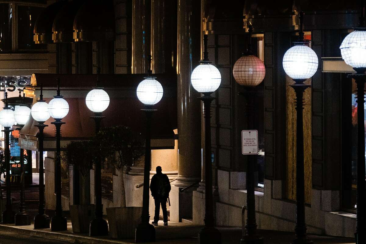 A pedestrian is seen walking past a row of streetlights in downtown San Francisco on Friday. PG&E wants to require technological upgrades at various facilities, including stoplights and streetlights, that would require the city to install meters and serve them with PG&E's power instead of electricity the city generates at Hetch Hetchy. City officials say the plan could cost $1 billion to implement.