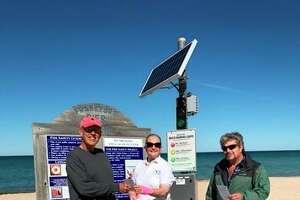 Carol Gunkler Johnson hands out water safety information near the SwimSmart warning light on Frankfort's beach. (Courtesy Photo)