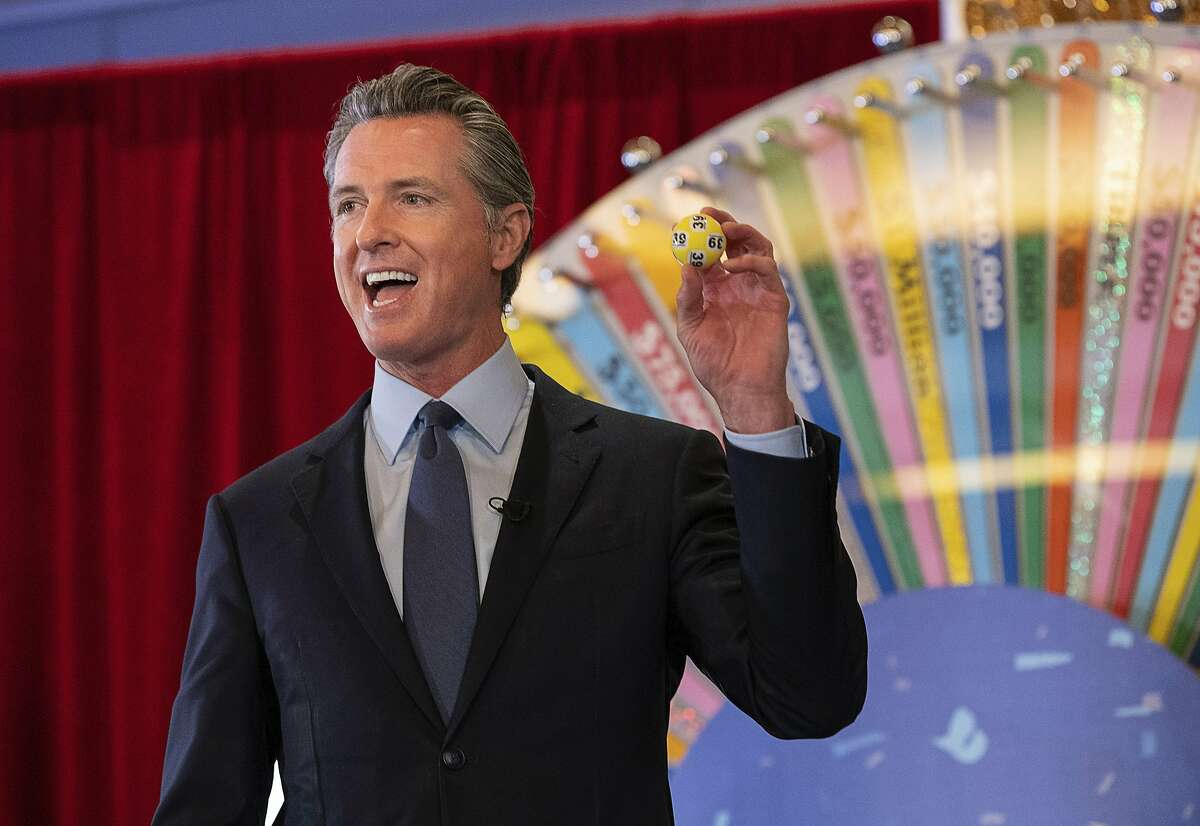 California Gov. Gavin Newsom holds up a lottery ball at the California Lottery headquarters on Friday in Sacramento while drawing numbers for California's new vaccine incentive lottery,