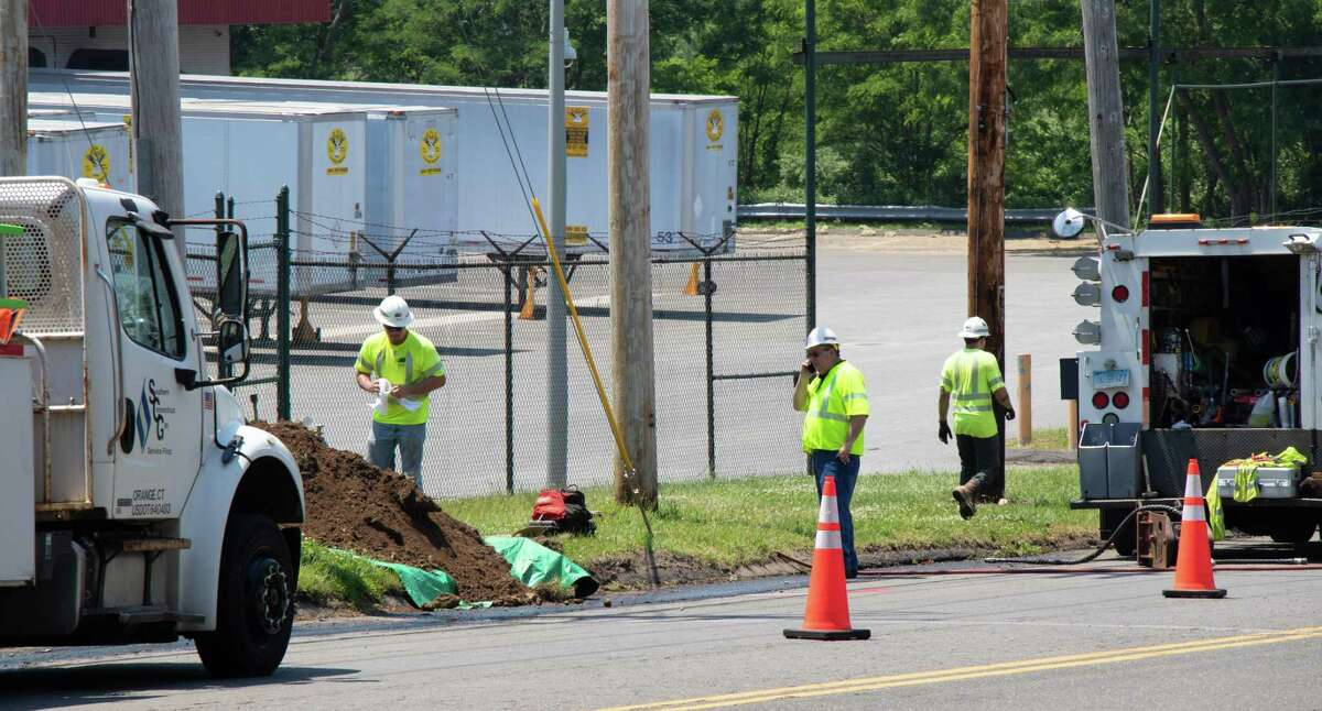 Utility workers fix a gas leak after a line ruptured Monday morning after being struck by a landscape worker.