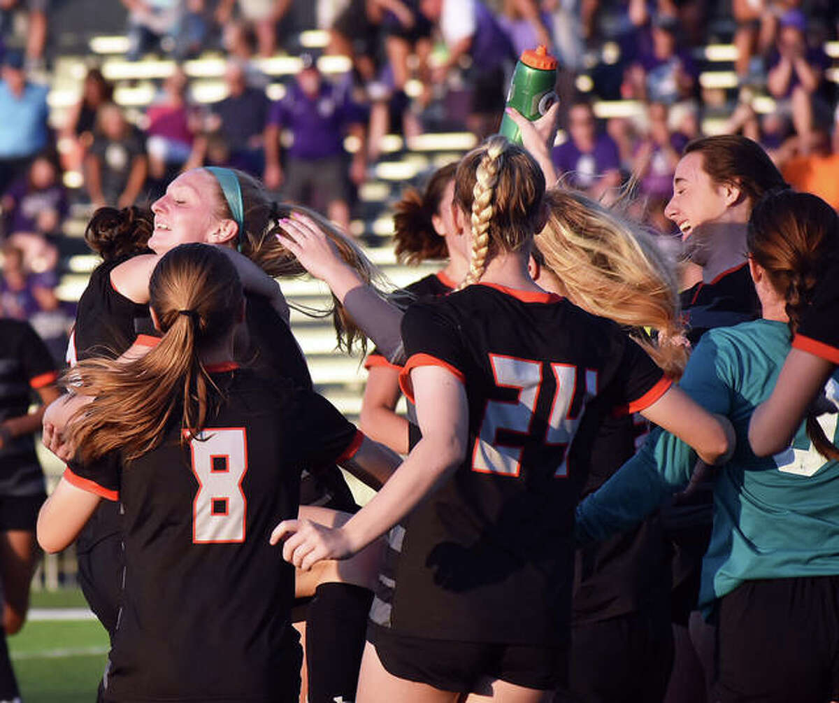 The Edwardsville Tigers celebrate after defeating the Collinsville Kahoks to win the regional championship on Friday inside the District 7 Sports Complex.