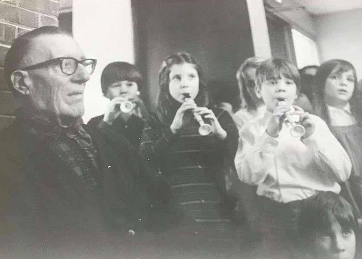 Edward Lightfoot listens to Cook Elementary School students sing Christmas carols. December 1976