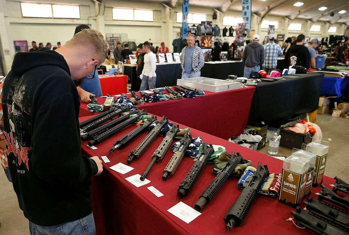Gun enthusiasts view AR-15 semi-automatic assault rifleparts and kits a 2015 gun show in Del Mar.