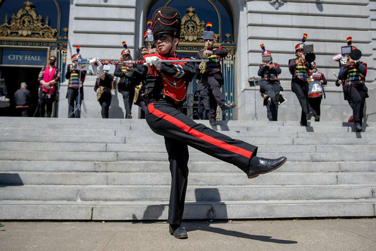 Mike Wong, conductor of the San Francisco Lesiban/Gay Freedom Band, dances along to the music as they perform during a Pride month kickoff celebration outside of San Francisco City Hall.