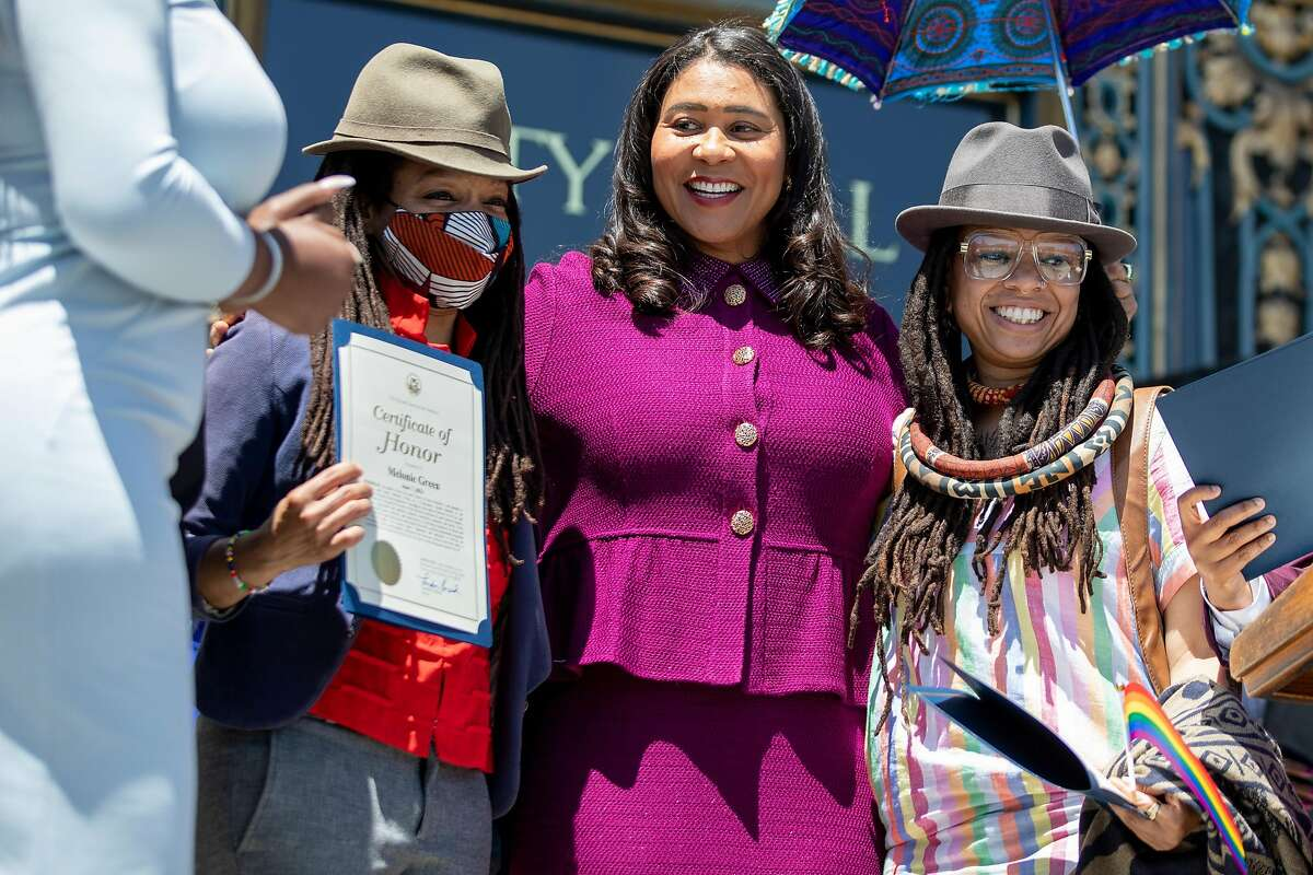Mayor London Breed presents San Francisco Pride Grand Marshals Melonie Green (left) and Melorra Green with official certificates of honor during a Pride month kickoff celebration outside of San Francisco City Hall.