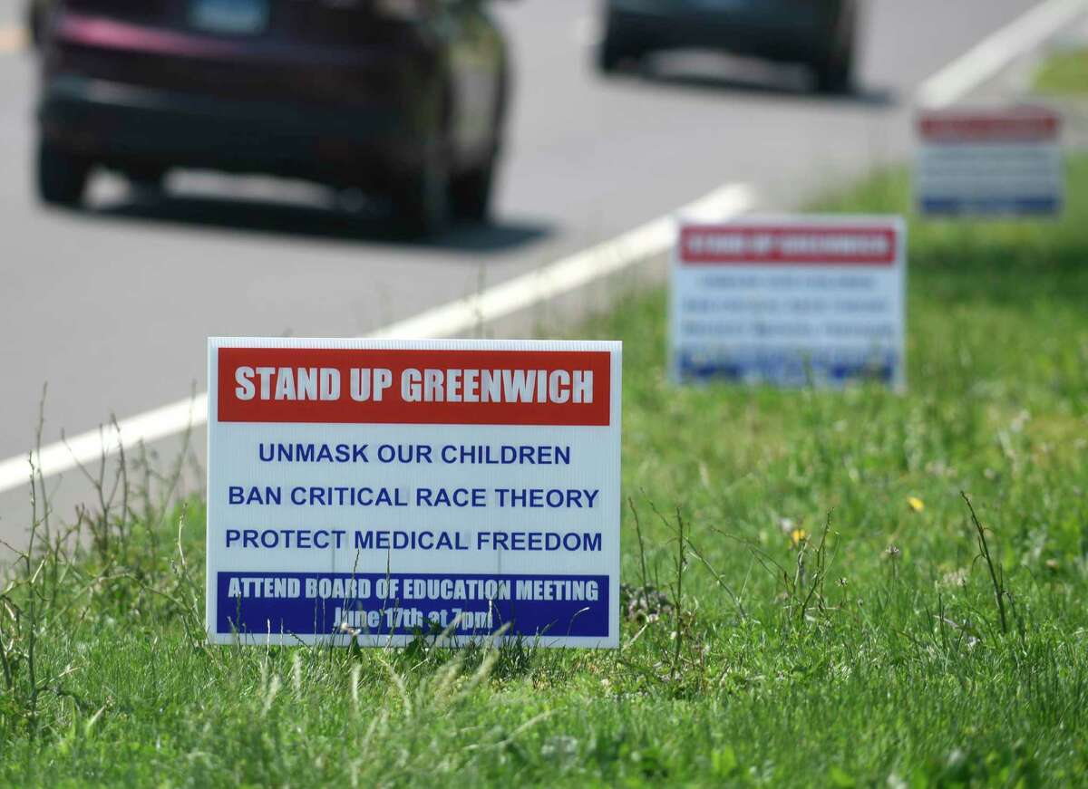 """Signs saying """"Unmask our children, ban critical race theory, protect medical freedom"""" are posted in the Riverside section of Greenwich, Conn. Monday, June 7, 2021."""