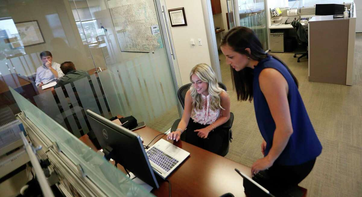 Brooke Petzold, left, an intern, works with analyst Eliza Klein at commercial real estate firm JLL, Monday, June 7, 2021, in Houston. A study by JLL shows people are ready to get back to the office, want flexibility in where they work, crave 'real' human interactions with colleagues and miss a change of scenery.