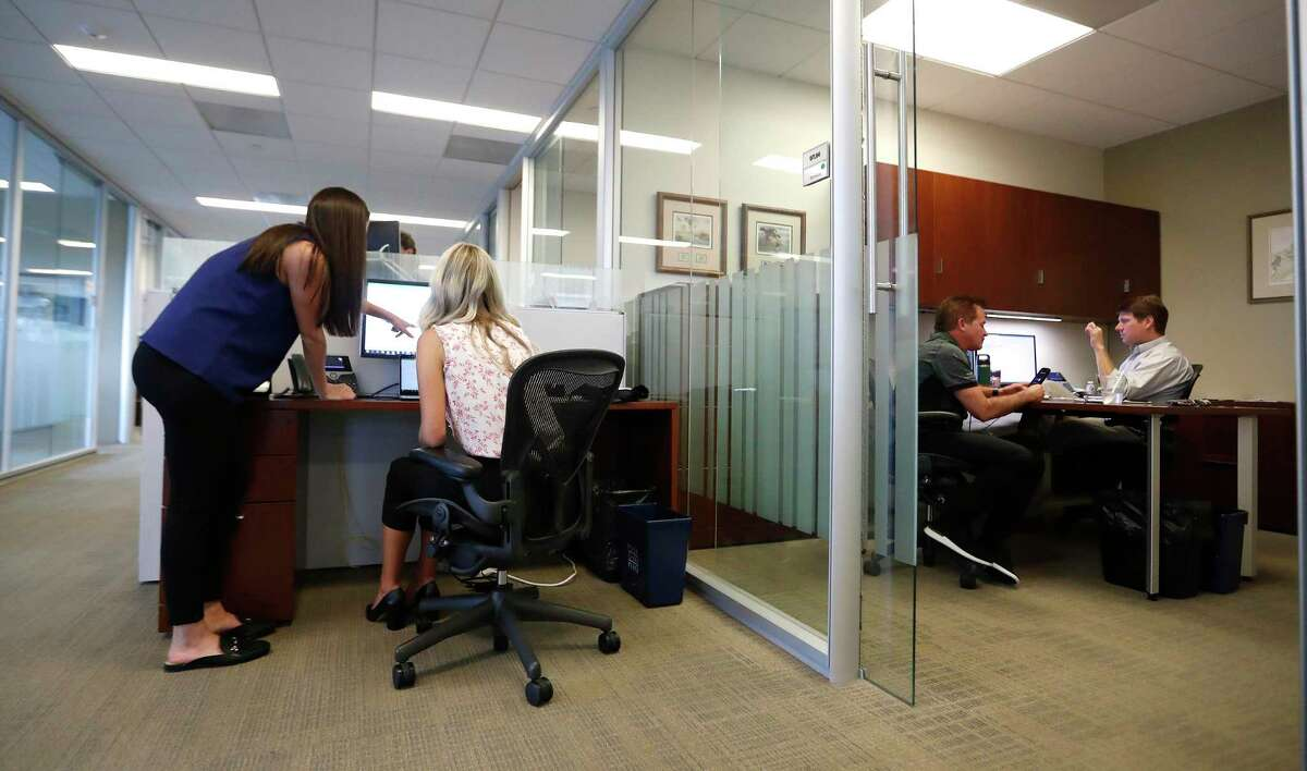 Analyst Eliza Klein, left, works with intern Brooke Petzold, right, at commercial real estate firm JLL, Monday, June 7, 2021, in Houston. A study by JLL shows people are ready to get back to the office, want flexibility in where they work, crave 'real' human interactions with colleagues and miss a change of scenery.