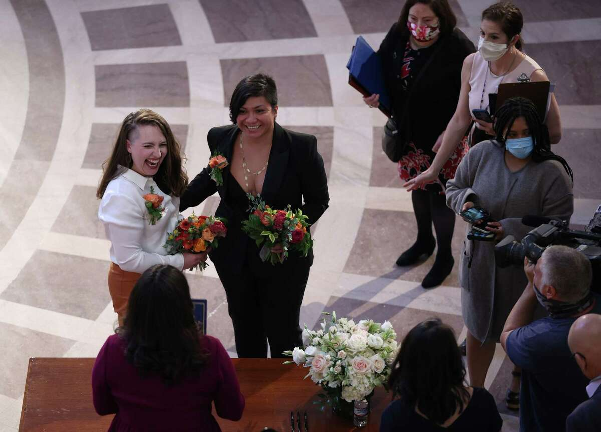 SAN FRANCISCO, CALIFORNIA - JUNE 07: Madelyn Peterson (L) and her partner Indira Carmona Muñoz (R) react after there were married by San Francisco Mayor London Breed (C) at San Francisco City Hill on June 07, 2021 in San Francisco, California. San Francisco City Hall reopened its doors to the public for the first time in 15 months after closing for the COVID-19 pandemic. The building was open for official business and San Francisco Mayor London Breed married four couples.