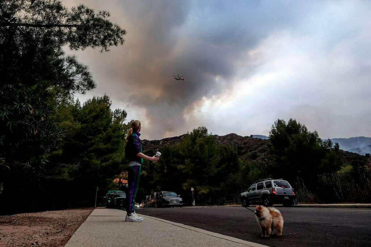 A woman with her dog watches as a plume of smoke rises from a wildfire in the Pacific Palisades area of Los Angeles, Sunday, May 16, 2021.