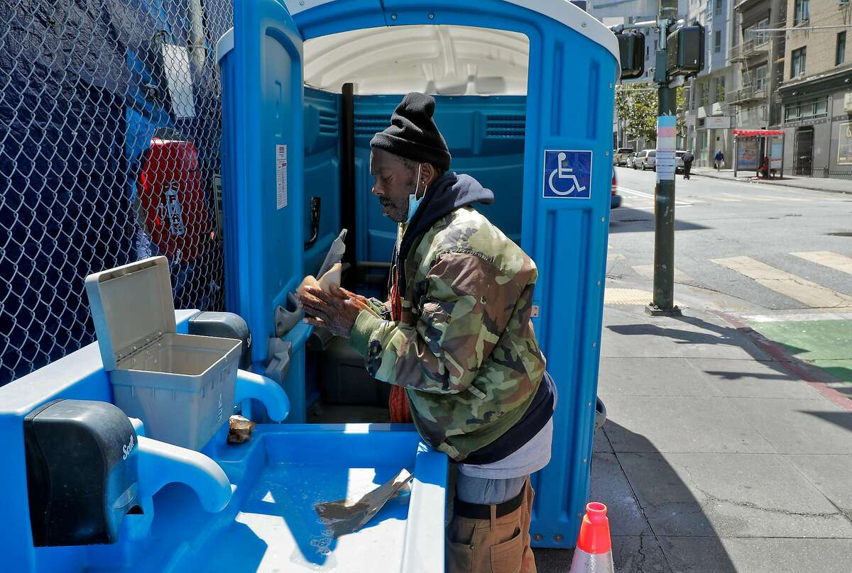 Dennis Prince washes his hands at several porta potties and hand washing stations that serve a homeless encampment on Turk and Jones Streets in San Francisco.