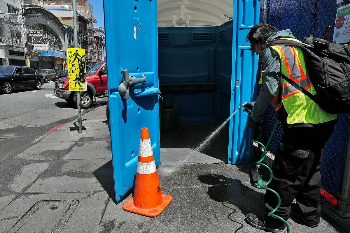 """A worker with Hunters Point Family who declined to give his name, cleans one of several porta potties and hand washing stations that serve a homeless encampment on Turk and Jones Streets in San Francisco, Calif., on Monday, June 7, 2021. The head of San Francisco's street homelessness response has been pushing the Department of Public Works to remove porta-potties set up during the pandemic as the city removes street encampments and rehouses homeless people in pursuit of the Mayor's desire for a """"tent free environment,"""" emails show."""