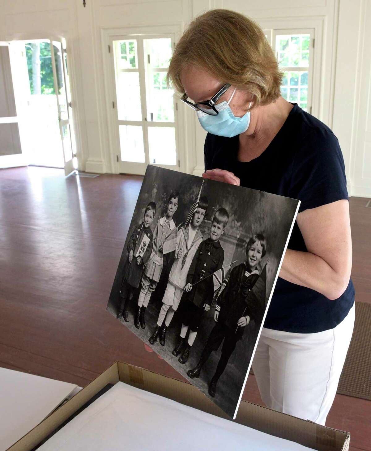 Hildegard Grob, executive director of the Keeler Tavern Museum, holds a print the museum had made from a Joseph Hartmann glass plate (negative on glass) that is part of their collection.