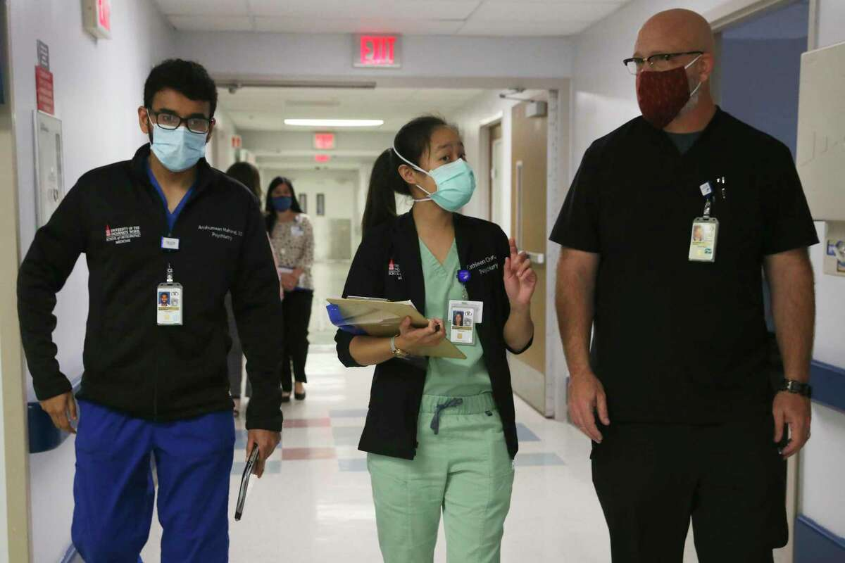 Psychiatric Resident Program Director Dr. Jason C. Miller, right, walks with residents Dr. Anshumann Majaraj, left, and Dr. Cathleen Chen at Texas Vista Medical Center on Tuesday, June 1. The hospital has teamed up with the University of Incarnate Word for a new internal medicine resident program.