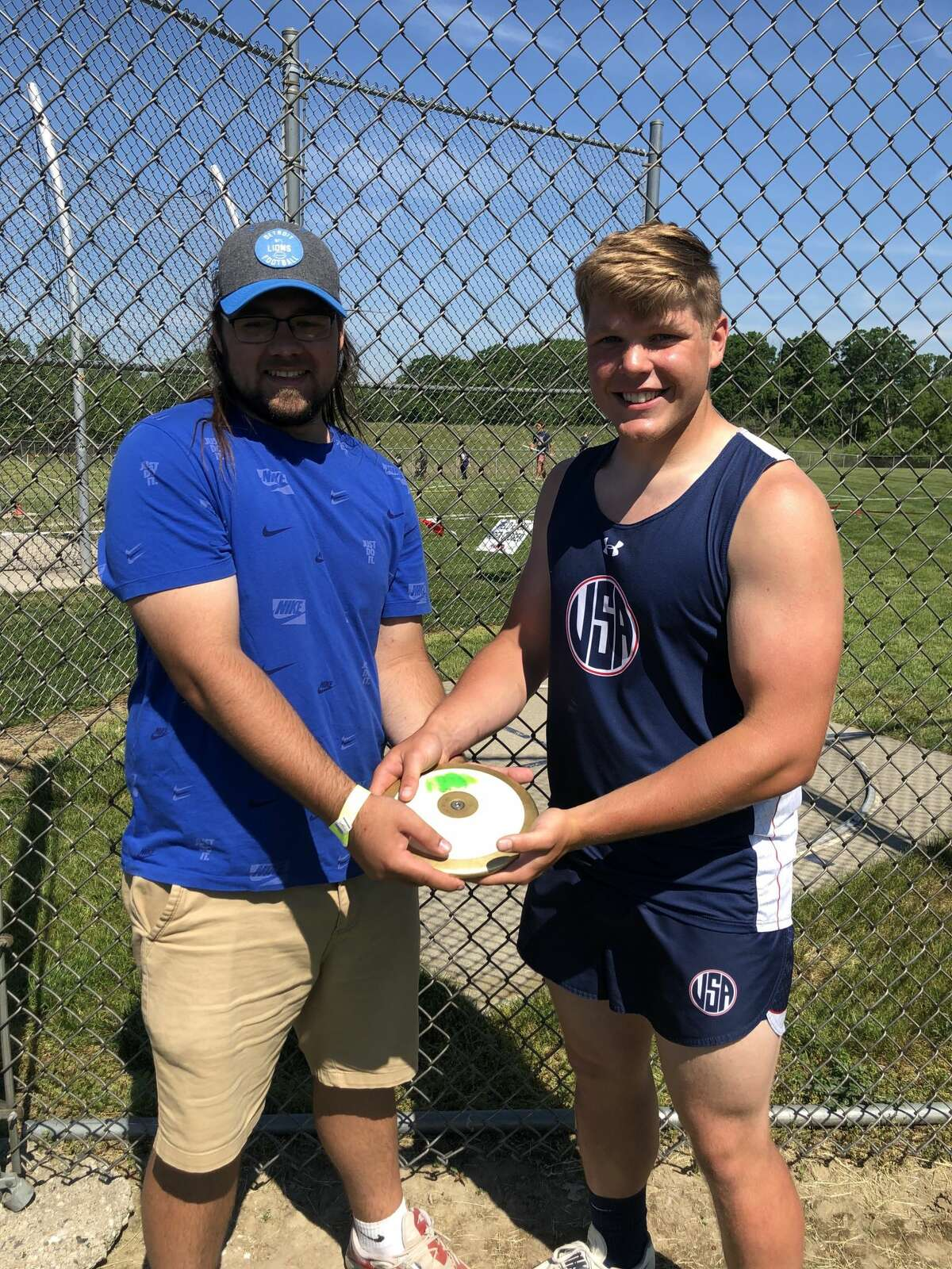 Jacob Nimtz of the Unionville-Sebewaing Area track team poses with his throws coach, Glenn Shook.