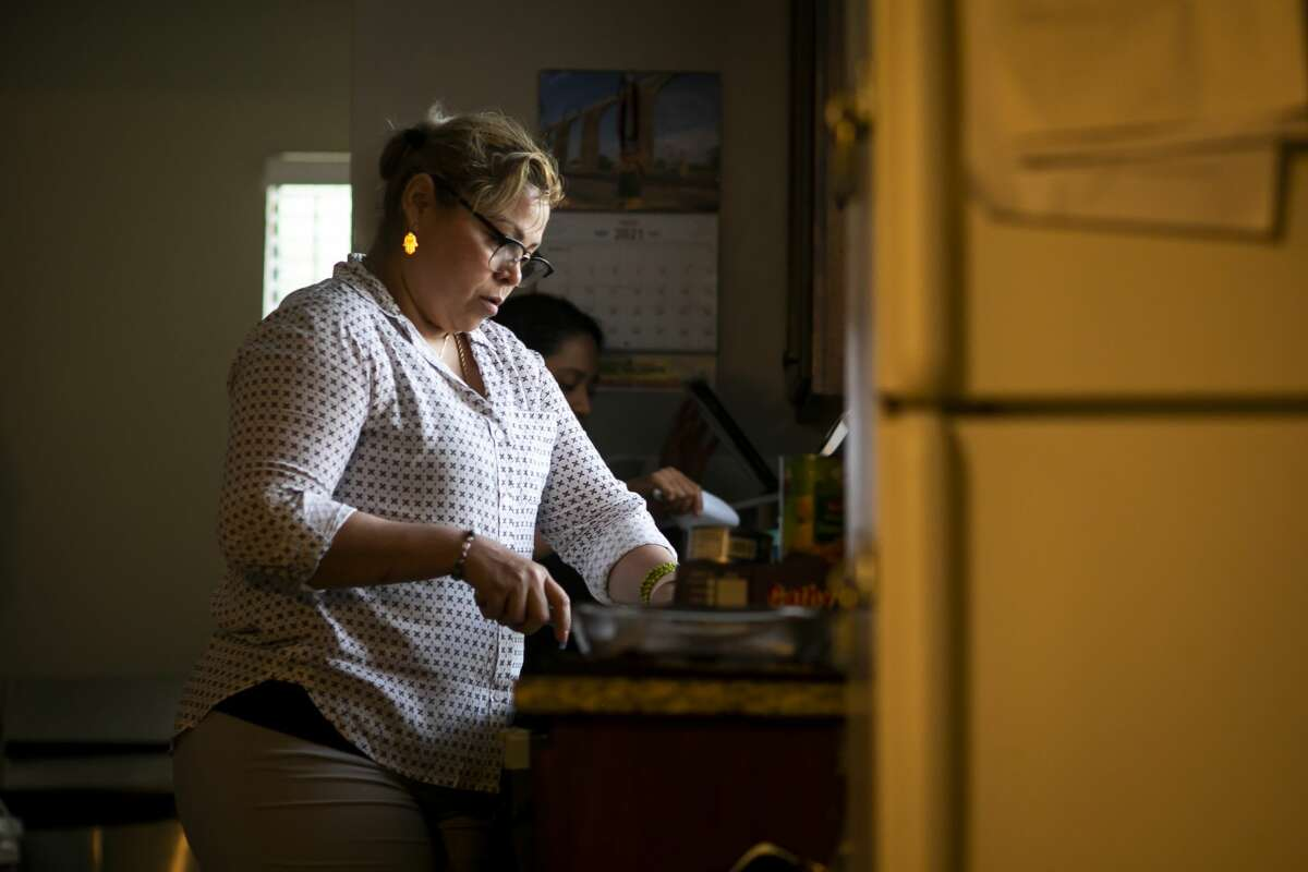 Clara Santos cuts up a lime of her daughter's dinner in her home on Monday, June 7, 2021.