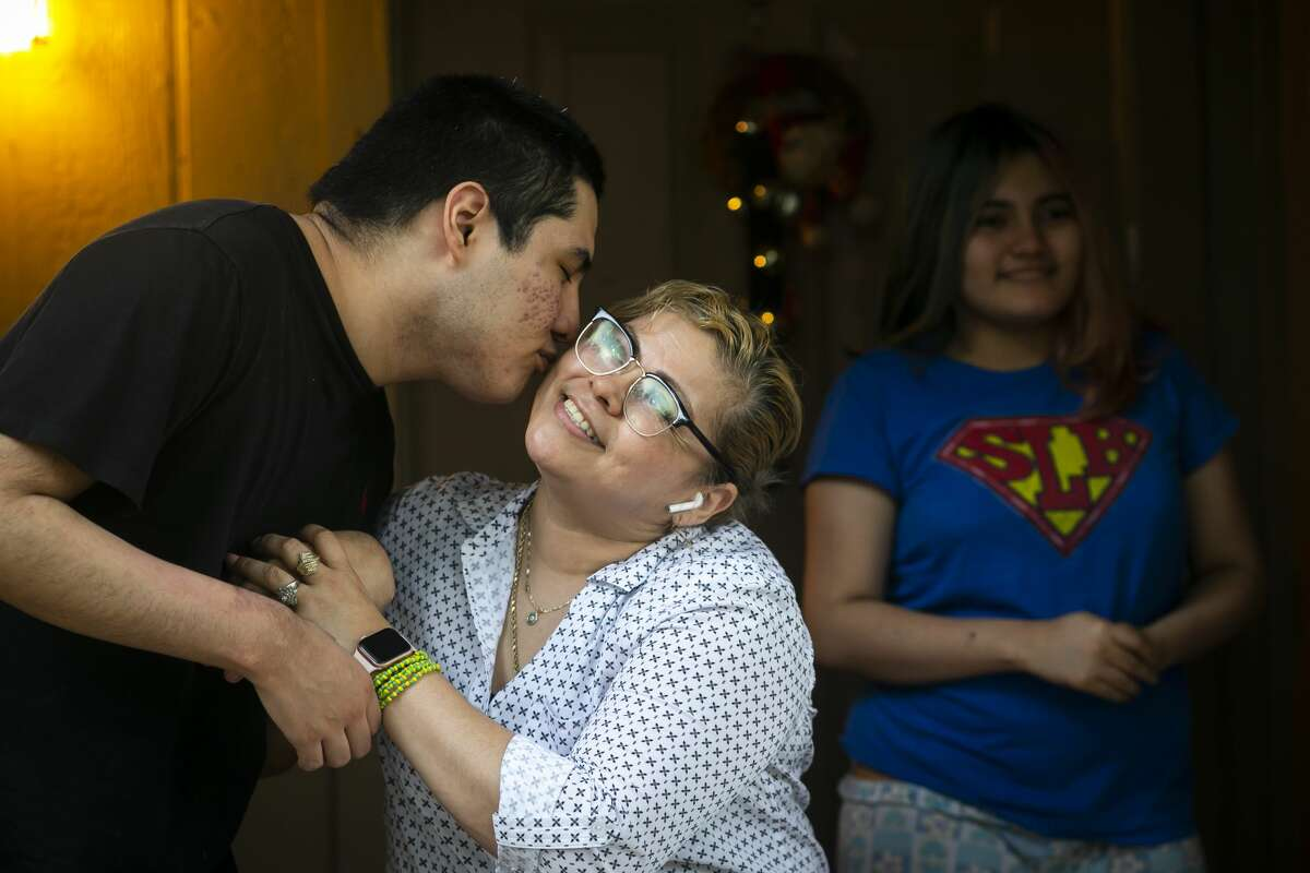 Jordan Diaz, 19, kisses his mother Clara Santos, outside of their Houston home on Monday, June 7, 2021. Santos came to the United States 25 years ago after suffering abuse in her home country of El Salvador. Santos was 14 when she arrived with three children while pregnant with the fourth. She now has seven children after eight pregnancies - six in Houston and one studying to be a doctor in El Salvador.
