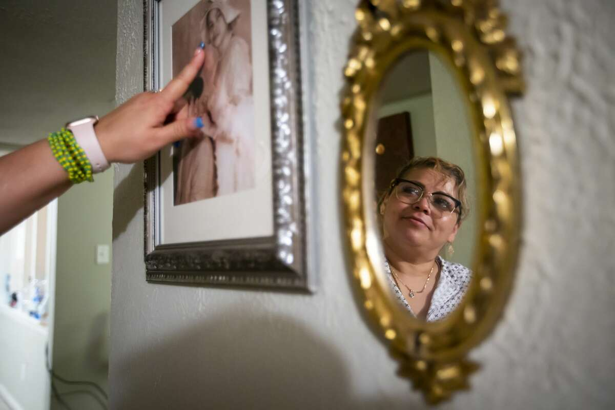 Clara Santos looks at a photograph of herself at a young age hanging in her Houston home on Monday, June 7, 2021.
