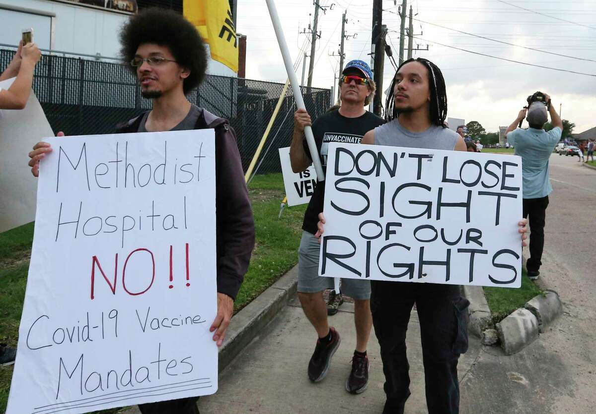 People march past protest Houston Methodist Baytown Hospital to protest against the hospital system's rule of firing any employee who is not immunized by Monday, June 7, 2021, in Baytown. Public and Houston Methodist staff who have refused the COVID-19 vaccine so far participated a gathering and march.