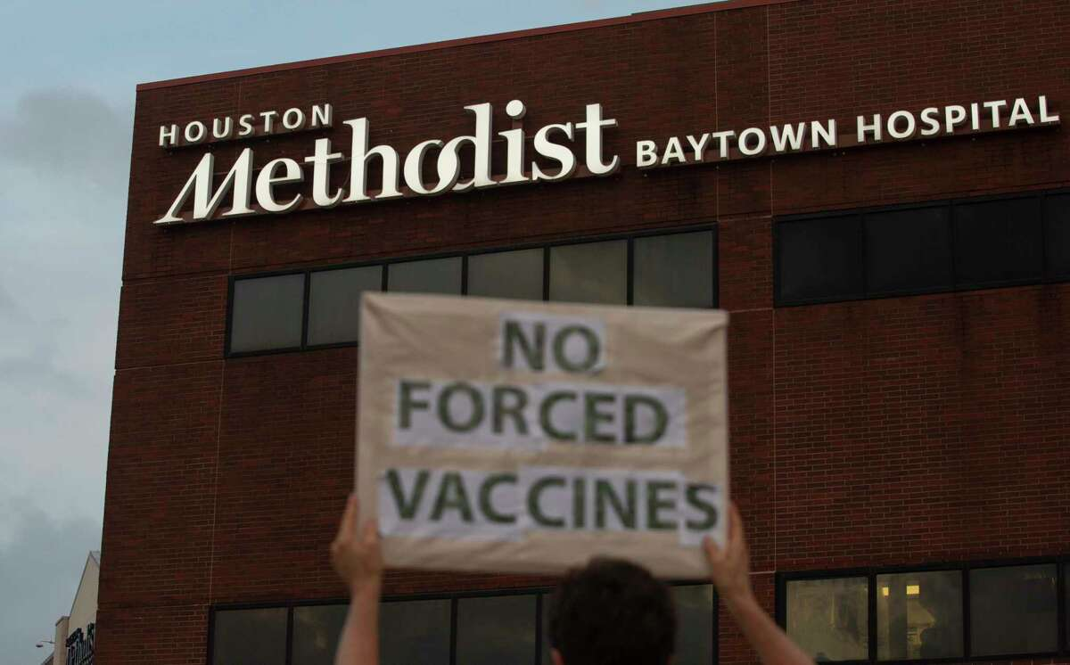 People bring signs to protest Houston Methodist Hospital system's rule of firing any employee who is not immunized by Monday, June 7, 2021, at Houston Methodist Baytown Hospital in Baytown. Houston Methodist staff who have refused the COVID-19 vaccine so far and their supporters participated a gathering and march.