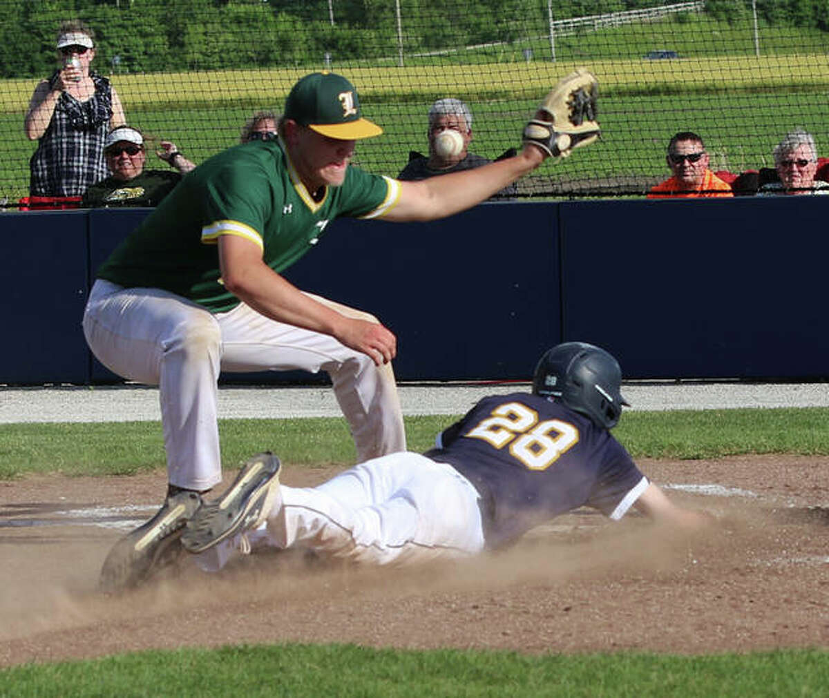 Father McGivney's Drew Sowerwine slides safely across home plate on a wild pitch in the fourth inning against Metro-East Lutheran.