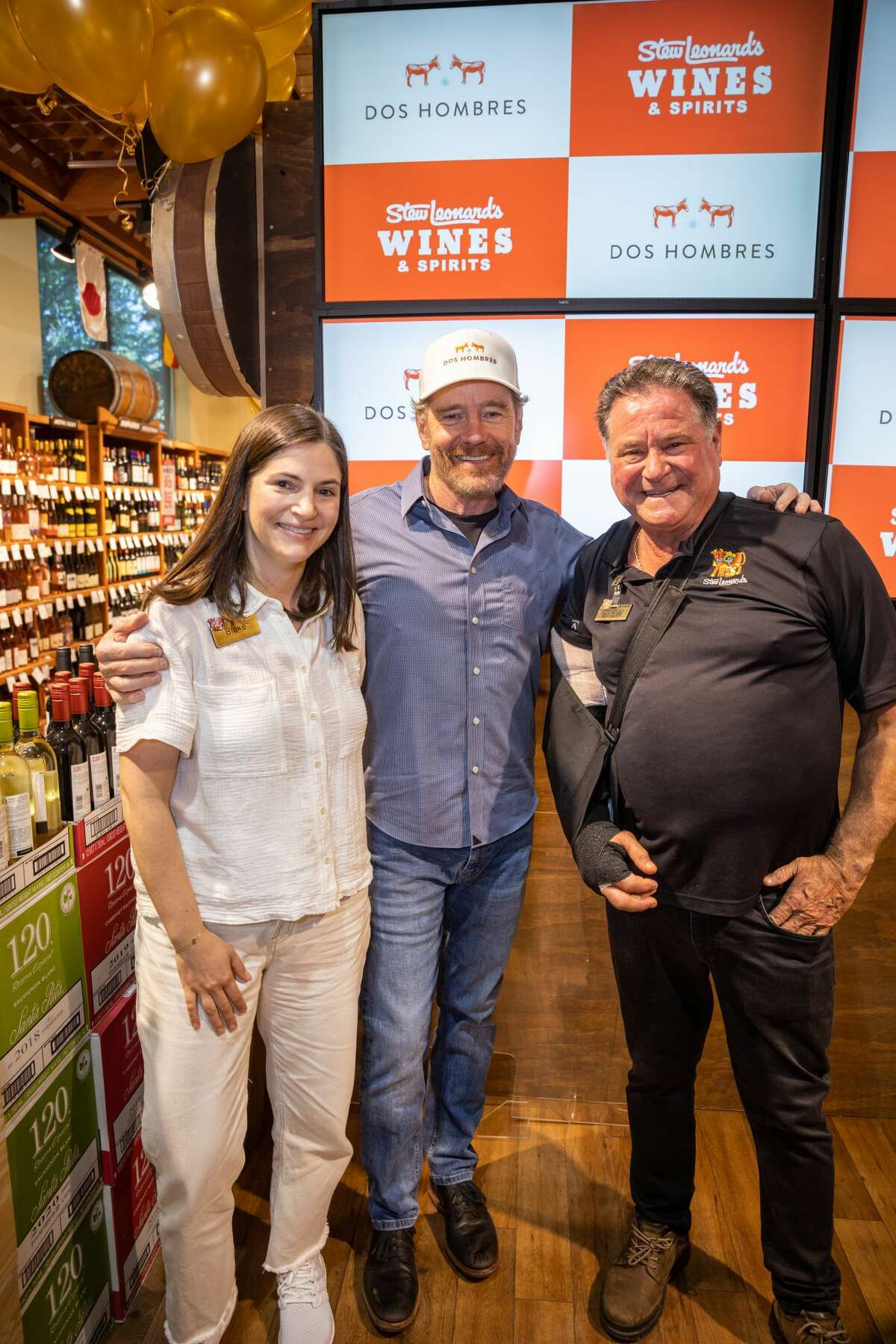 Actor Bryan Cranston with Blake Leonard, certified sommelier and VP of Stew Leonard's Wines and Spirits and Stew Leonard Jr., President & CEO of Stew Leonard's at Stew Leonard's in Norwalk on June 7, 2021.