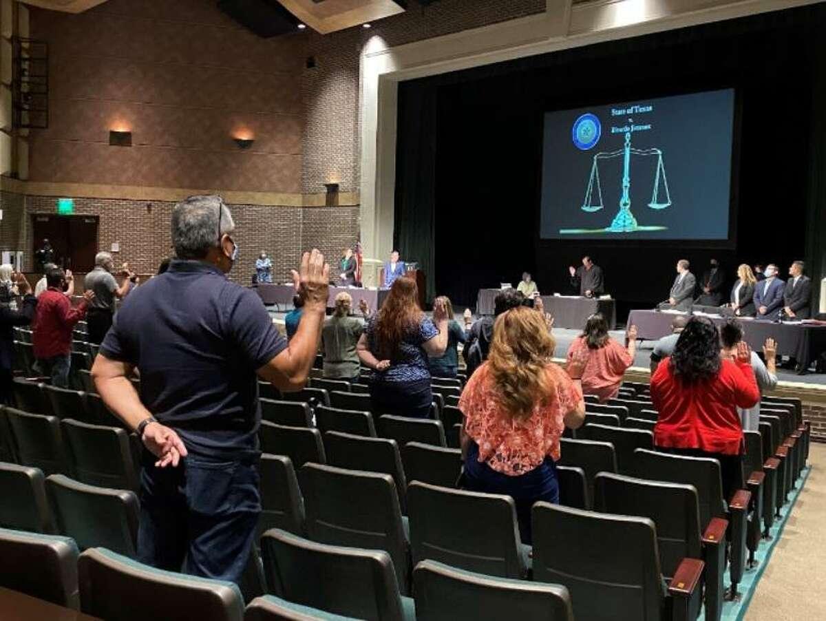 Potential jurors raise their right hands at Laredo College's Martinez Fine Arts Center.