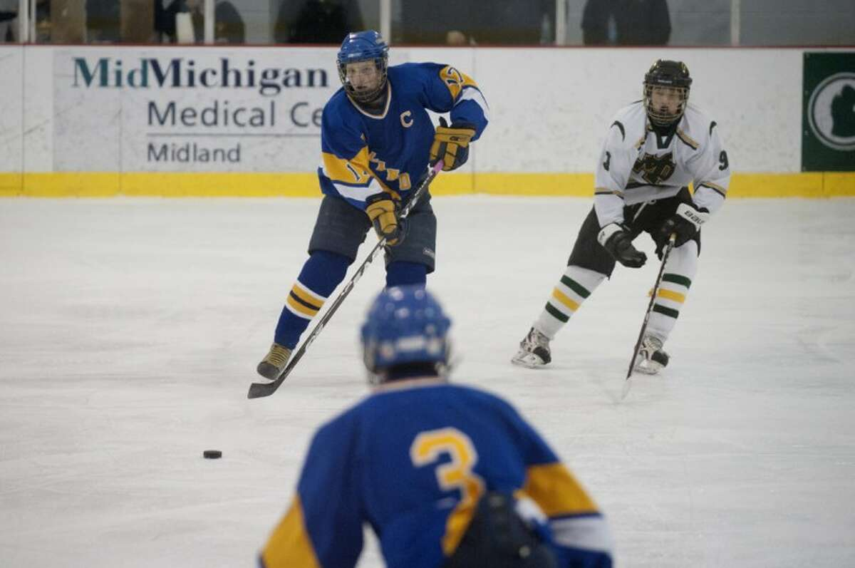 Midland High's Nick Mammel carries the puck up the ice during a Feb. 9, 2012 game against Dow High.