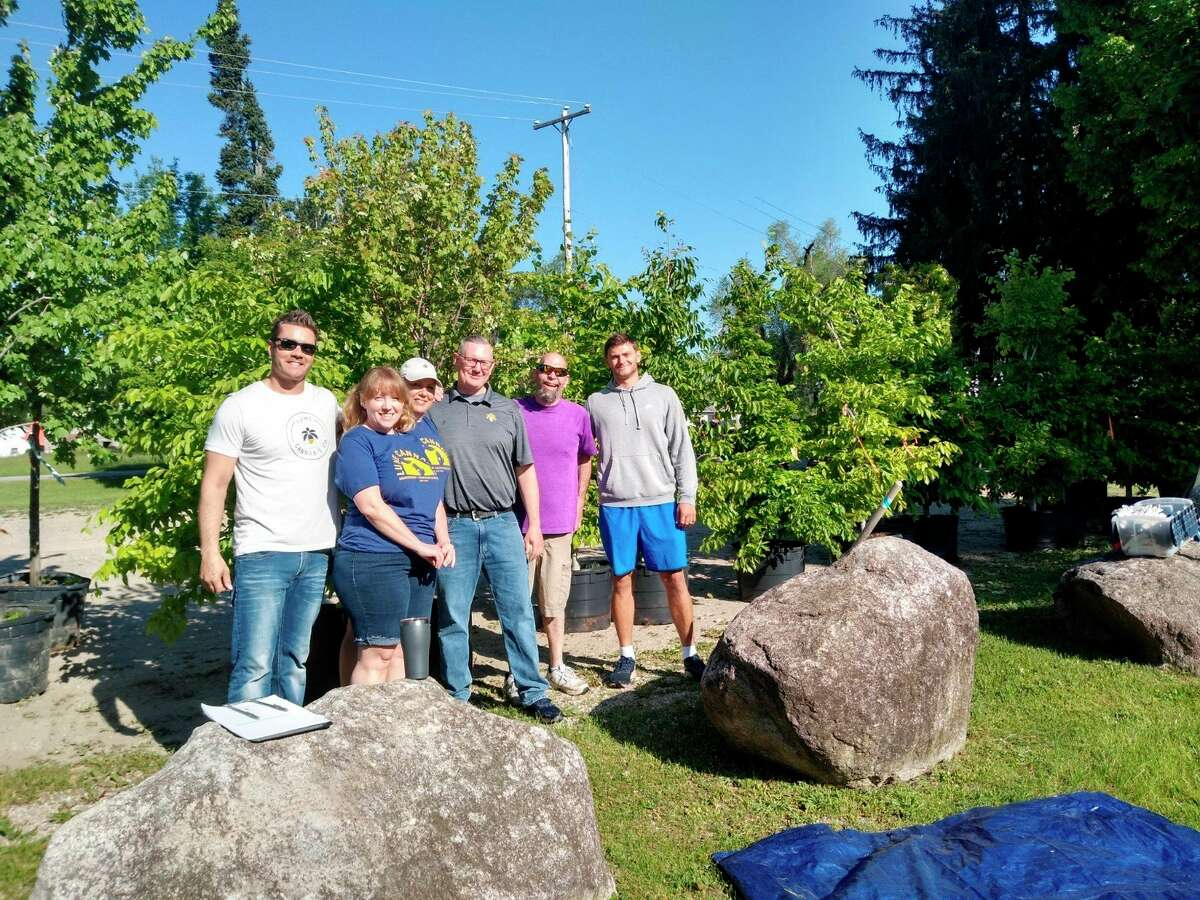 Volunteers from Lume Cannabis Company in Evart prepare to begin the tree planting around the city parks and neighborhoods. Lume provide 60 volunteers to help with the effort. (Photo courtesy of the city of Evart)