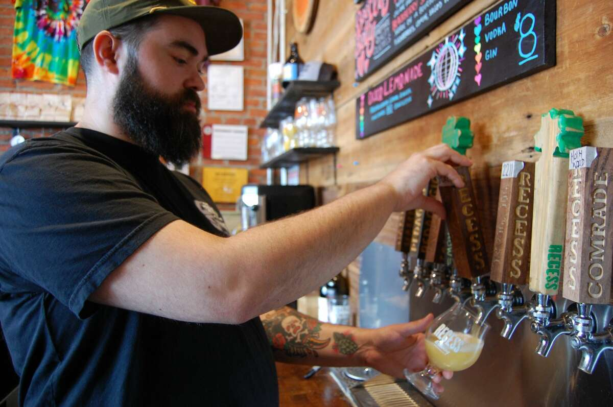 Tracy Hutton, head brewer at Recess Brewing, carefully pours a beer from the tap.