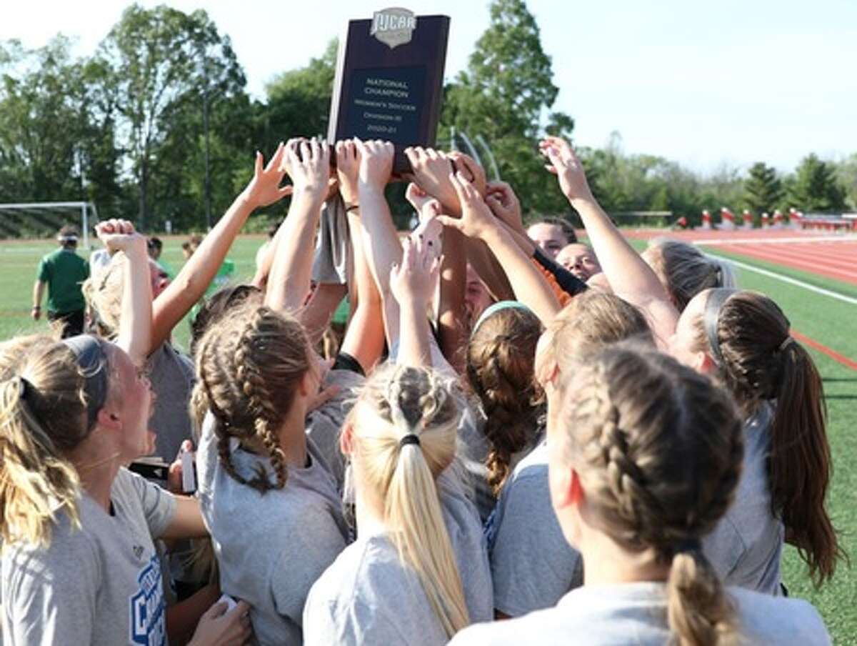 Members of Delta College's women's soccer team celebrate with the championship trophy after winning the NJCAA Division III national title on Saturday.