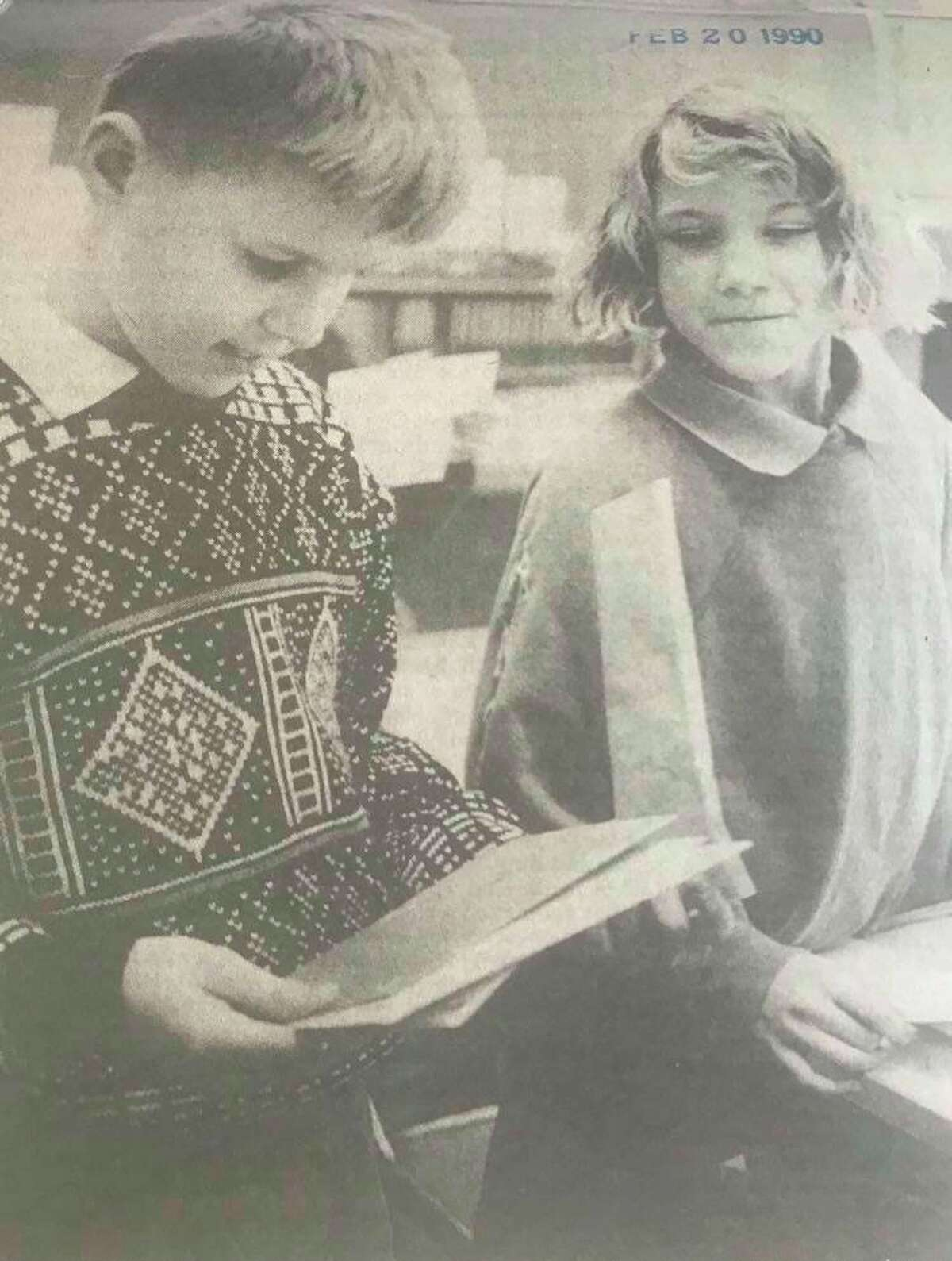 Scott Pugh, a member of Cook Elementary School Student Council, delivers Valentine's Day mail to Angie Sambrook, another third grader. February 1990