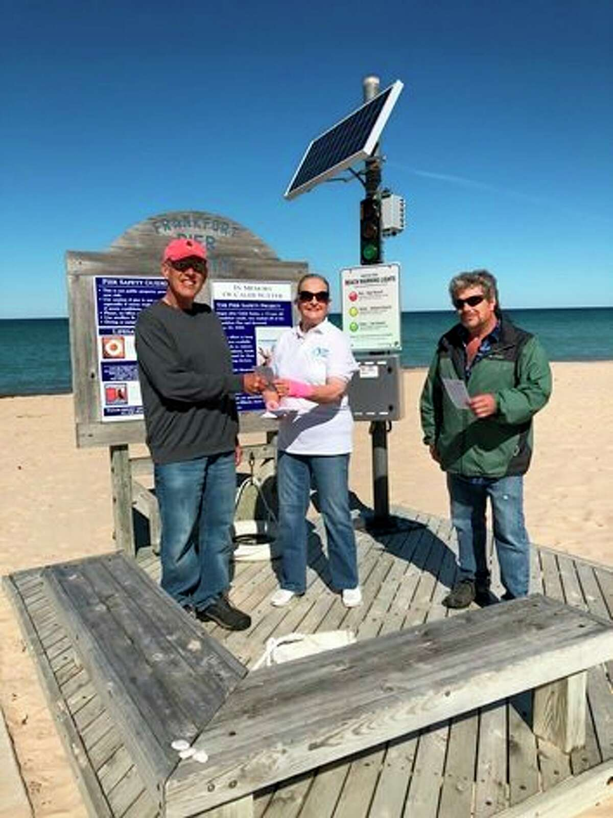 Carol Gunkler Johnson hands out water safety information by the SwimSmart warning light on Frankfort's beach (Courtesy Photo)