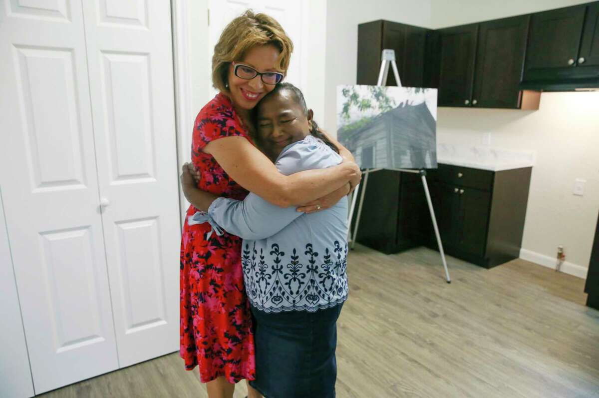 San Antonio City District 5 Councilwoman Shirley Gonzales, left, hugs Laura Martinez, 61, after handing her the keys to her house Monday. Martinez's modified shotgun house, nearly 100 years old, was in disrepair and was renovated through a city program.