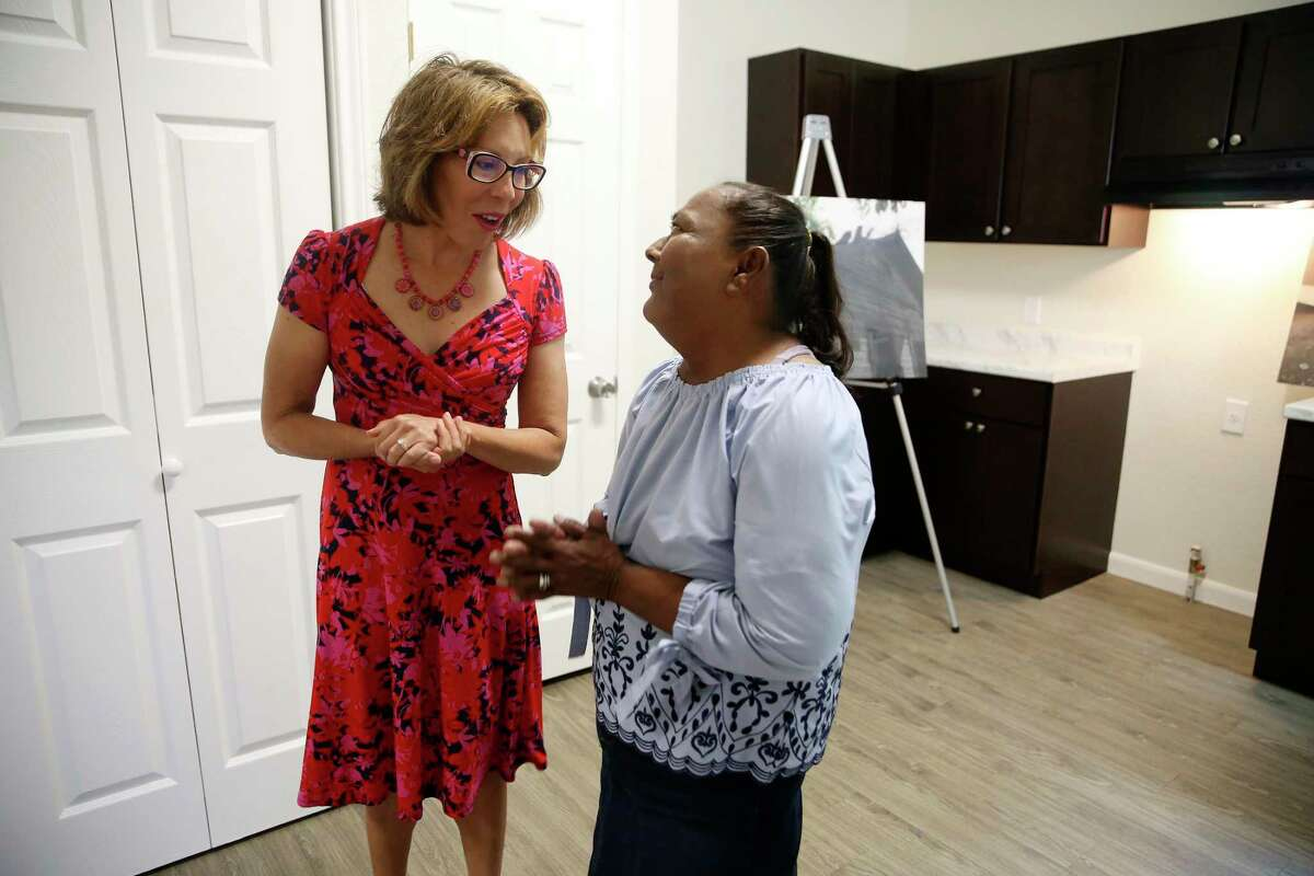 San Antonio City District 5 Councilwoman Shirley Gonzales, left, talks with Laura Martinez, 61, after handing her the keys to her house on Monday. Martinez's modified shotgun house, nearly 100 years old, was in disrepair and was renovated through a city program.
