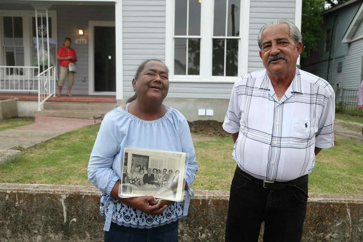 Humberto Martinez, 71, and his wife, Laura, 61, stand in front of their renovated home in the Harris neighborhood near downtown San Antonio on Monday. The home was unlivable but was renovated through a city program. They are holding a photograph of Humberto Martinez's grandfather, who purchased the home after the Great Depression.