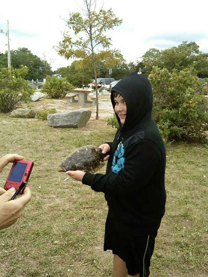 A participant in the Fairfield Police Athletic League Snapper-Blue derby holds up a fluke he caught on Saturday, Sept. 11, 2010. Photo: Contributed Photo / Fairfield Citizen contributed
