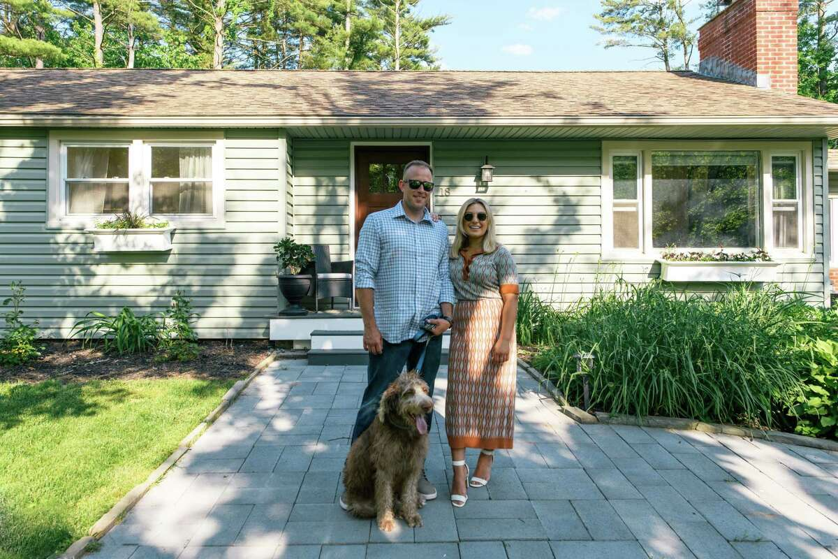 Keith Sweeney and Taylor Rao (with their dog, Jet) moved quickly when it came to buying their first house. The couple was impressed with the curb appeal of the house, featuring a recently redone front entryway, as well as new garage doors and a front door. Photo by Beth Mickalonis