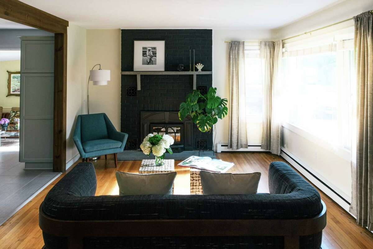 Rao and Sweeney's first project was to paint all the interior walls. The traditional brick fireplace got a modern update with a paint called limousine leather. (Photo by Beth Mickalonis)